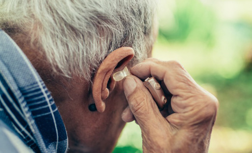 An elderly man puts in his hearing aid